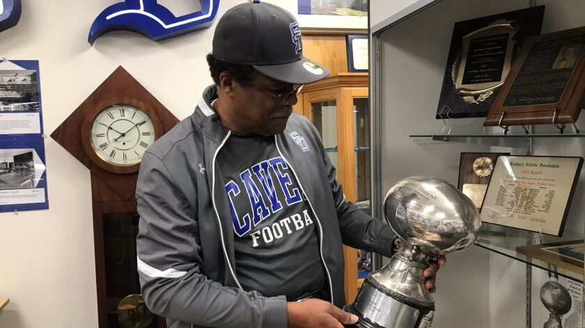 San Diego High assistant football coach Eddie Head II holds the Evening Tribune Perpetual Trophy.