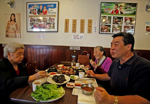 Choon Do Park, left, Young Soon and Joon Yoo dine at Jangchung-Dong Wong Jokbal in Los Angeles' Koreatown.