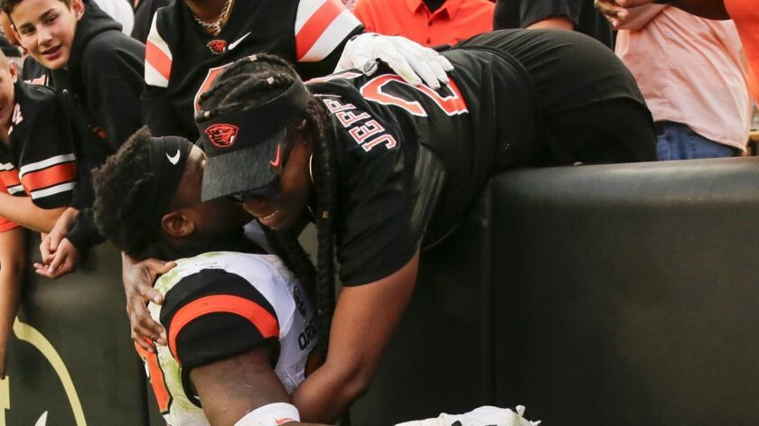Oregon State Beavers running back Jermar Jefferson hugs his mother following a win against Colorado