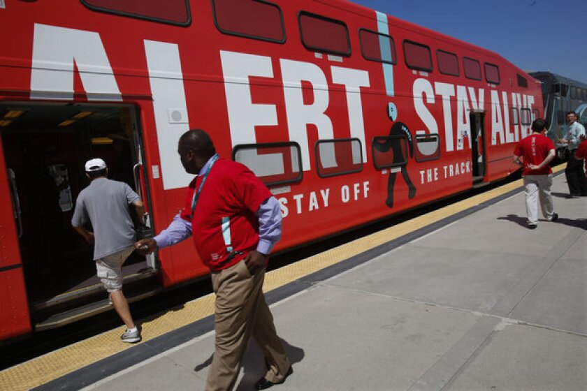 Members of the public check out a Metrolink train at Union Station in Los Angeles that has been wrapped in a warning sign for Rail Safety Month.