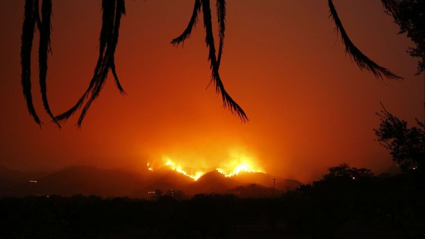 CARPENTERIA, CA – DECEMBER 12, 2017: Fire burns back down the hill behind East Valley Road by Lad