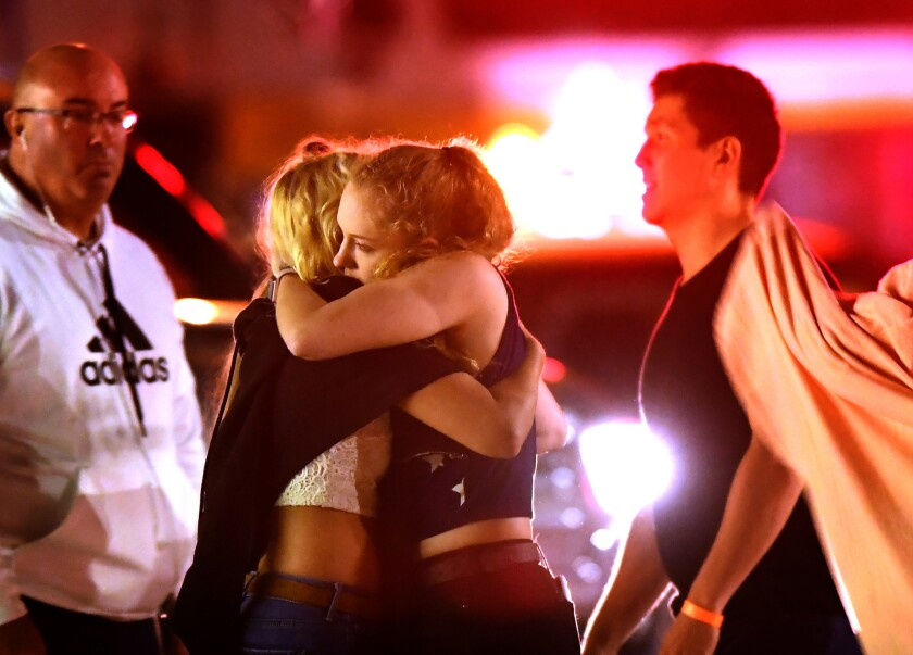 People comfort each other after a mass shooting at the Borderline Bar & Grill in Thousand Oaks late Wednesday night.
