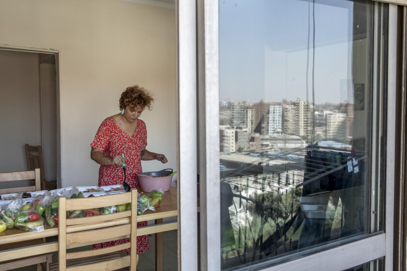 """Basma Mostafa, a 30-year-old journalist who founded an initiative that sends freshly home cooked meals to quarantined coronavirus patients, package food at her friend's apartment, in Cairo, Egypt. Saturday, July 11, 2020. Mostafa, who works with others to coordinate the volunteer effort, said she got the idea of helping out when she was going through a difficult time. """"I thought that to alleviate my suffering, I can engage with the suffering of others and feel more for them,"""" she said. """"I derive my strength and perseverance from the patients."""" (AP Photo/Nariman El-Mofty)"""