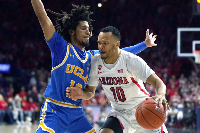 Arizona guard Jemarl Baker Jr., right, drives on UCLA guard Tyger Campbell during the second half of the Bruins' upset win Saturday.