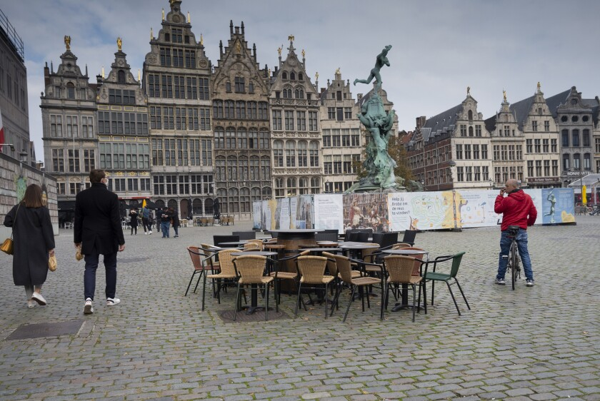 FILE - In this Monday, Oct. 20, 2020 file photo, people walk by chairs and tables of an empty terrace in the historical center of Antwerp, Belgium. Belgian health authorities warned Friday, Feb. 26, 2021 that the number of coronavirus infections is rising as the government appeared set to prolong restrictions for several more weeks. (AP Photo/Virginia Mayo, File)
