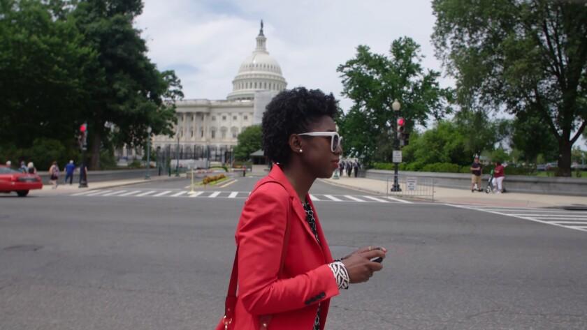 "MIT researcher Joy Buolamwini walking in Washington, D.C., in the documentary ""Coded Bias."""