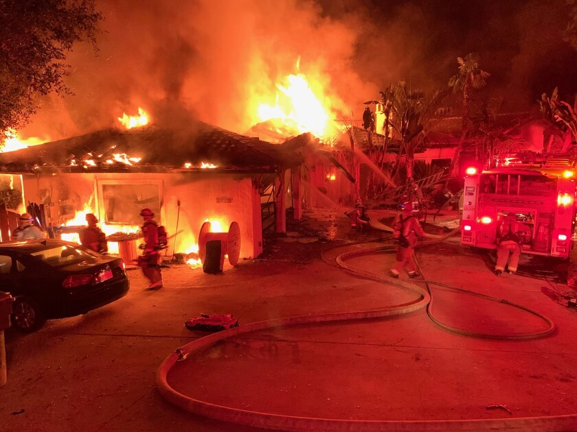 Firefighters battle flames tearing through an Escondido home Friday morning. The house caught fire again Friday evening