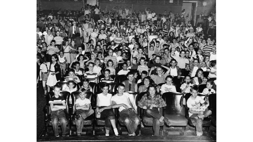 An audience of mostly children cheer and make faces in a movie theater, mid 1950s.