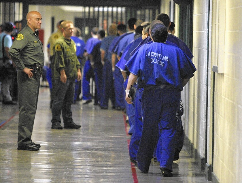 Staff members watch inmates at the Los Angeles County jail. Nearly 5,000 people in state prison and tens of thousands more in county jails and on probation are probably eligible for resentencing.
