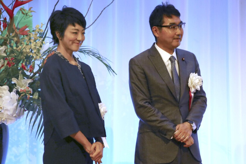 Japan's former Justice Minister Katsuyuki Kawai and his lawmaker wife Anri Kawai stand on stage at a political fundraising party in Hiroshima, western Japan, on Sept. 23, 2019. The couple was arrested Thursday, June 18, 2020, over allegations they engaged in vote buying during last year's election. Prosecutors arrested the couple on suspicion that they offered millions of yen in cash to dozens of voters ahead of the 2019 upper house election in which Anri Kawai won a seat, officials and media reports said. (Kyodo News via AP)
