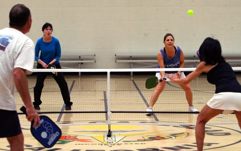 Vicki Stone, center right, waits for the ball hit by opponent Reiko Siniscal, right, as they play pickelball with their partners Patty Elia, left center, and Gary Dwelley earlier this year at Calavera Hills Community Center in Carlsbad. Photo by Bill Wechter