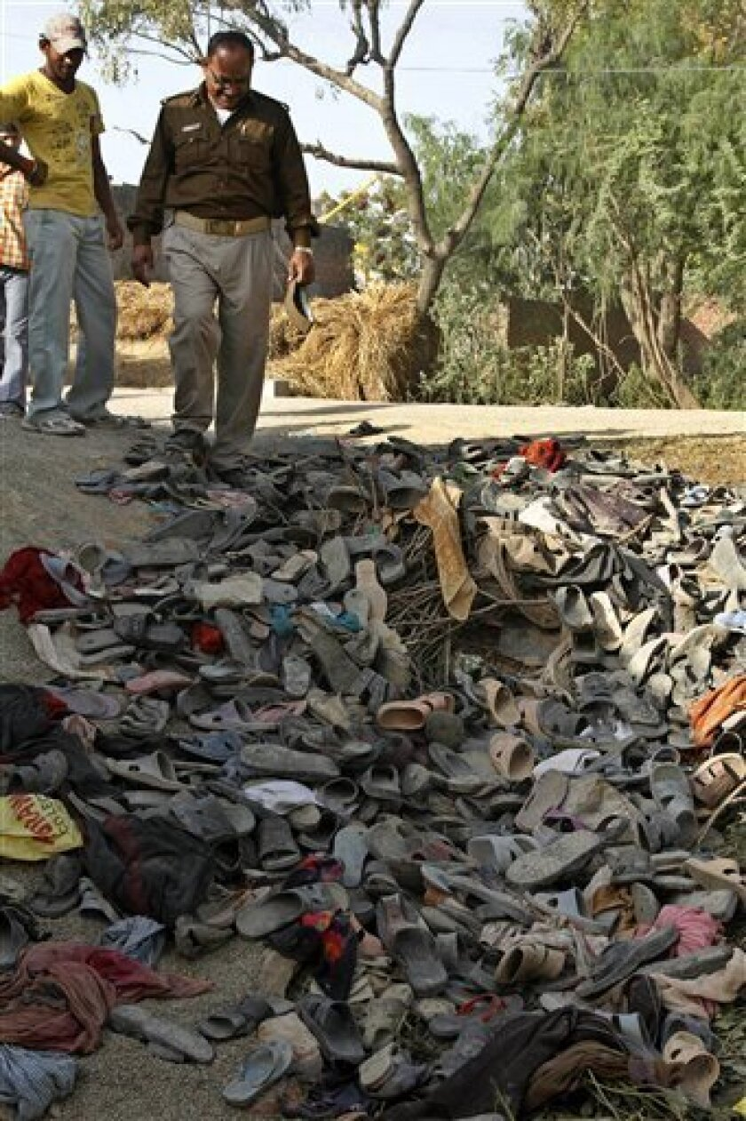 An Indian police officer surveys the scene as shoes and sandals are seen after a stampede at a temple in Kunda, 180 kilometers (112 miles) southeast of Lucknow, Uttar Pradesh state, India, Thursday, March 4, 2010. Scores of people were killed and dozens of others injured in the stampede that broke out Thursday as thousands of people jostled each other to get free clothes and utensils being distributed during a religious function at the temple in north India, officials said. (AP Photo/Rajesh Kumar Singh)