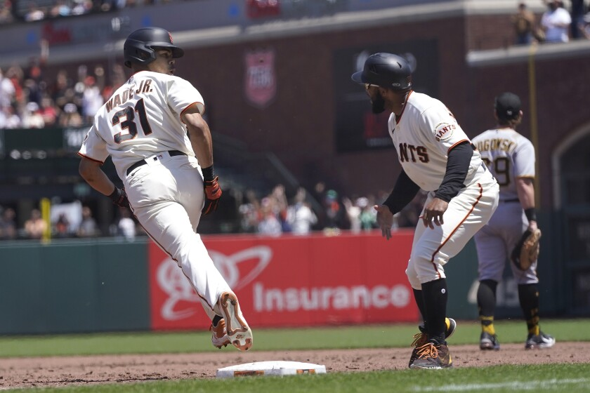San Francisco Giants' LaMonte Wade Jr, left, reacts toward first base coach Antoan Richardson after hitting a home run against the Pittsburgh Pirates during the third inning of a baseball game in San Francisco, Sunday, July 25, 2021. (AP Photo/Jeff Chiu)