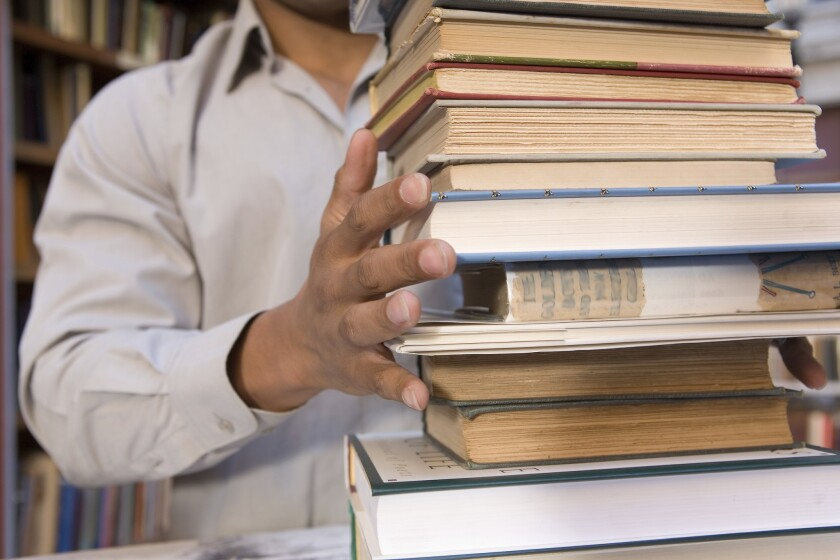 College student with large stack of books ** TCN OUT ** ** TCN OUT ** ORG XMIT: 25FHPIC