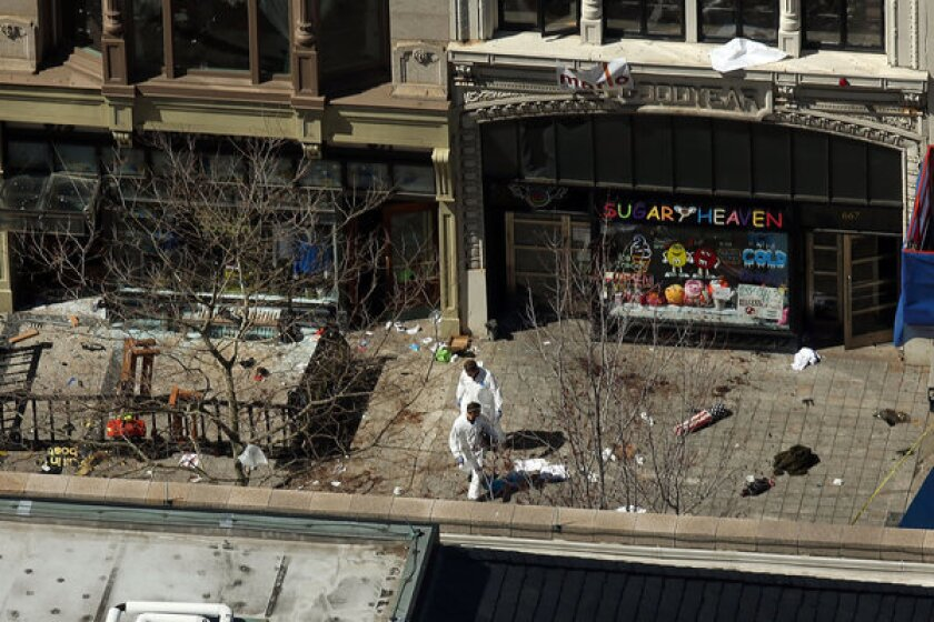 Investigators stand at the scene of bombings at the Boston Marathon on Wednesday. The explosions, which occurred Monday near the finish line of the 116-year-old race, resulted in the deaths of three people, with more than 170 others injured.