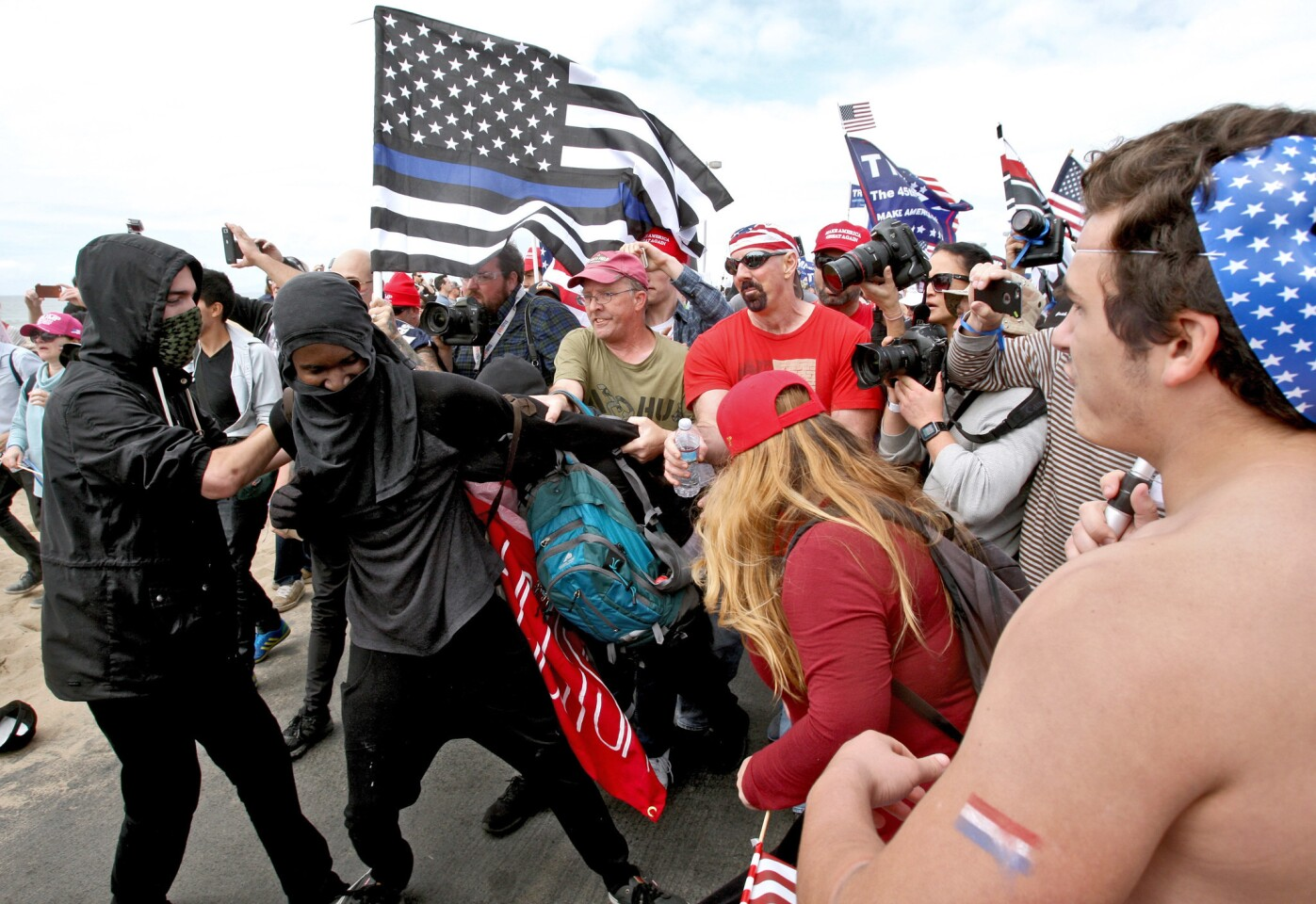A protester is pulled by the Make America Great Again March crowd at Bolsa Chica State Beach in Huntington Beach on Saturday. The march was in support of President Trump.