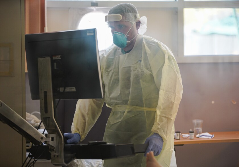 A person wearing personal protection equipment stands in front of a computer.