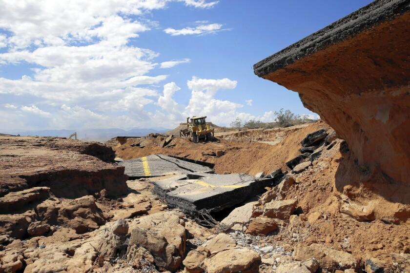A bulldozer works on a flood-ravaged portion of Interstate 15 near Moapa, Nev.