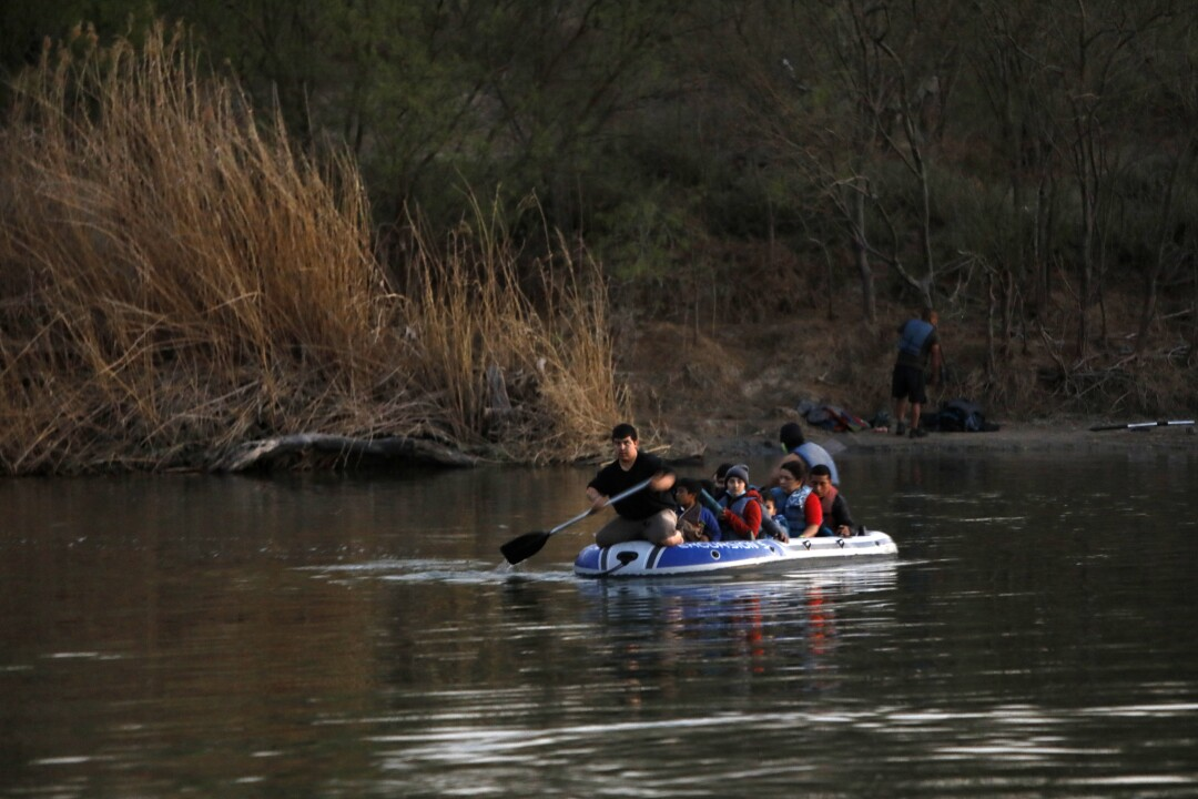 Asylum seekers are transported across the Rio Grande by smugglers on a raft