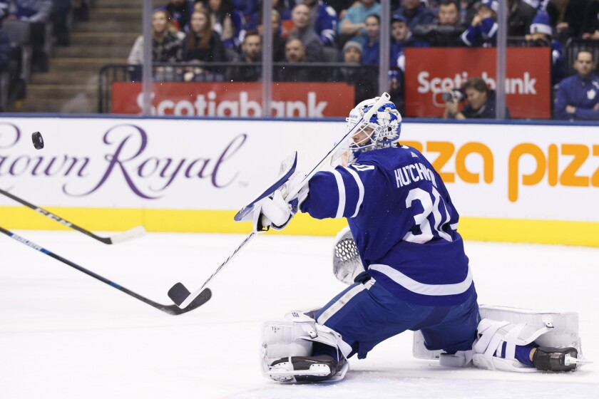 Toronto Maple Leafs goaltender Michael Hutchinson (30) makes a stop against the New York Islanders during the first period of an NHL hockey game Saturday, Jan. 4, 2020, in Toronto. (Cole Burston/The Canadian Press via AP)