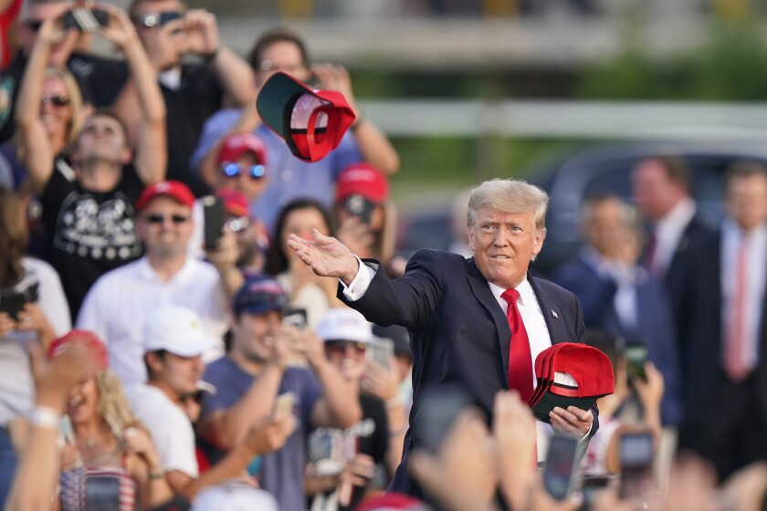 Former President Trump throws red hats into the audience at the Lorain County Fairgrounds in Wellington, Ohio.