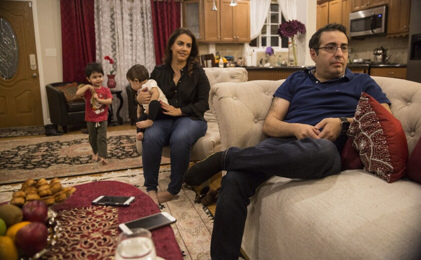 Arian Edalat, right, with wife Samah, son Neema, 3, and daughter Nava, 10 months, talks about the Trump travel ban and his difficulties to bring his mother, a recent visa recipient, to the U.S.