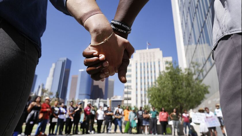 LOS ANGELES, CA - OCTOBER 04, 2016 - Pastor Cue Jn-Marie, right, and Taylor Fisher, left, hold hands