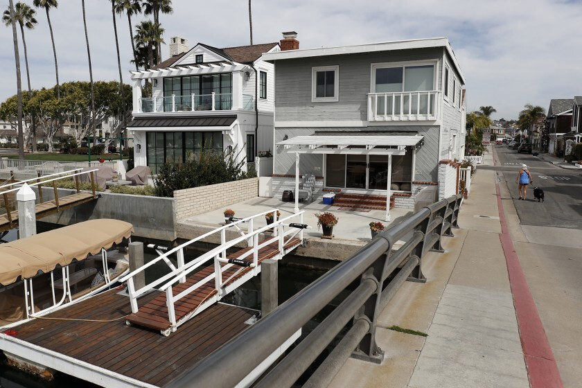 A woman walks her dog past a waterfront duplex on 38th Street on Newport Island. The duplex is reportedly used as a vacation rental.