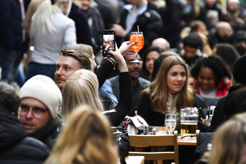 Woman taking photo of her cocktail