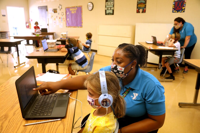 Denecia Boone, a teacher with the YMCA, helps a student with an exercise at Anza Elementary School