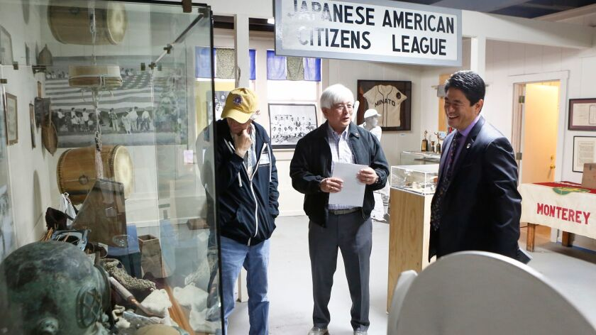 Japanese American Citizens League board members Tim Thomas, left, and Larry Oda speak with Mitchell
