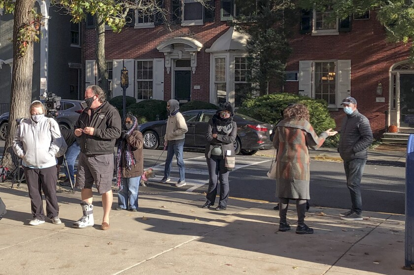 Voters wait in line outside the Bucks county government building in Doylestown, Pa., a suburb of Philadelphia, on Monday, Nov. 2, 2020. Some said they received word that their mail-in ballots had problems and needed to be fixed in order to count. (AP Photo/Mike Catalini)