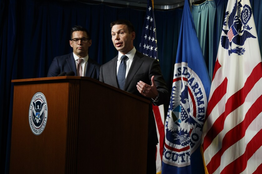 Department of Homeland Security (DHS) Acting Secretary Kevin McAleenan, right, is joined by public affairs spokesman Andrew Meehan, as he speaks during a news conference in Washington on Friday.
