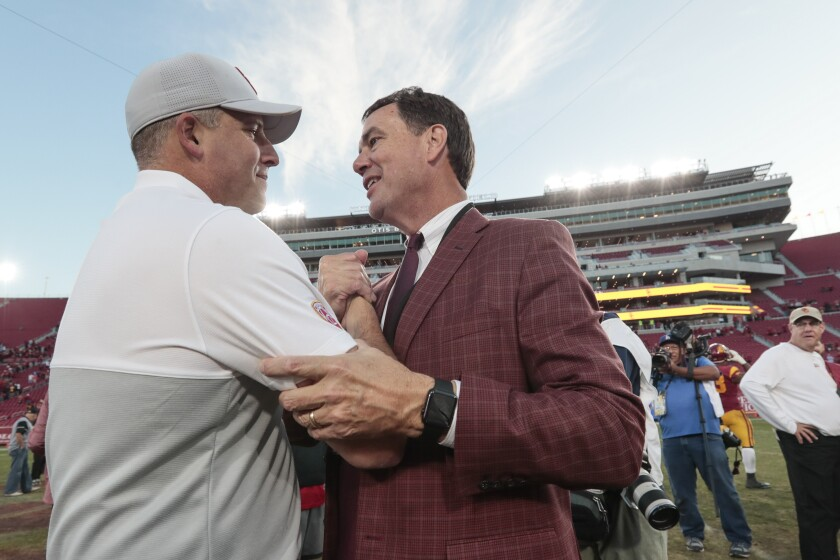 USC head coach Clay Helton is congratulated by Athletic Director Mike Bohn at midfield after a 52-35 win over UCLA at the Coliseum on Nov. 23, 2019.