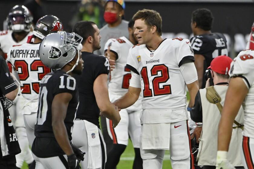 Tampa Bay Buccaneers quarterback Tom Brady (12) greets Las Vegas Raiders quarterback Derek Carr (4) after an NFL football game, Sunday, Oct. 25, 2020, in Las Vegas. (AP Photo/David Becker)