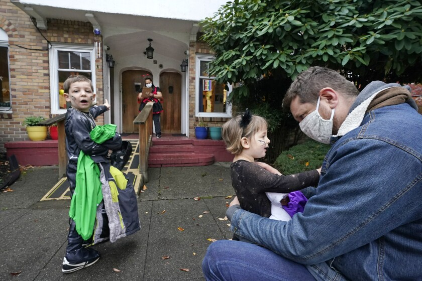 Alex Stonehill gets a goodbye from his daughter Helenore, 2, as her brother Malcolm, 4, motions to a friend arriving at the Community Day Center for Children on Thursday, Oct. 29, 2020, in Seattle. As more families make the jump back to group day care this fall in an attempt to restart lives and careers, many parents, pediatricians and care operators are finding that new, pandemic-driven rules offer a much-needed layer of safety but also seem incompatible with the germy reality of childhood. (AP Photo/Elaine Thompson)