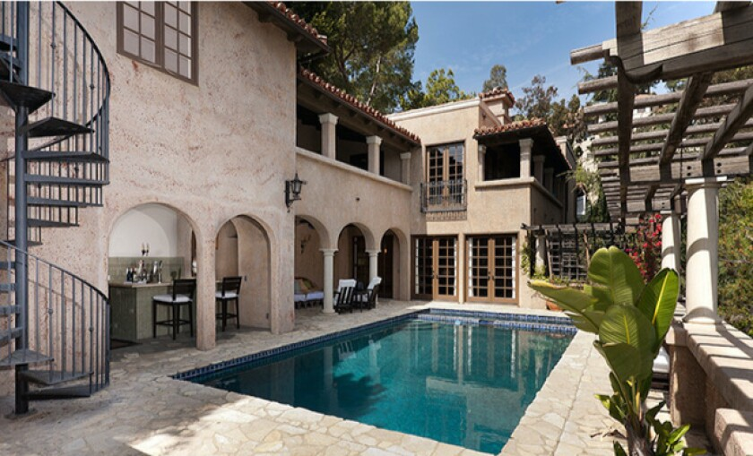 Gated and landscaped, the two-story villa boasts a dramatic courtyard entry and charming backyard with a pool.