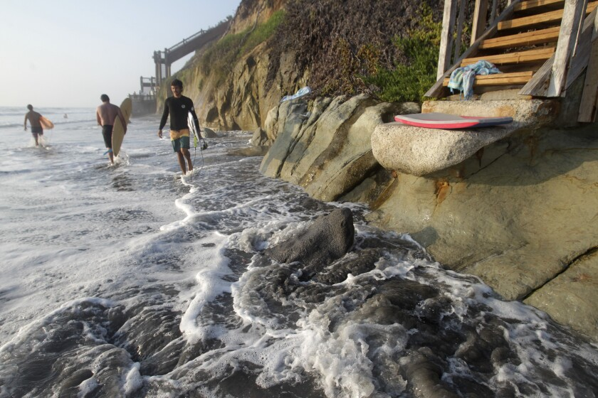 High-tide waters hit the base of the bluffs at Grandview beach in north Encinitas Thursday.