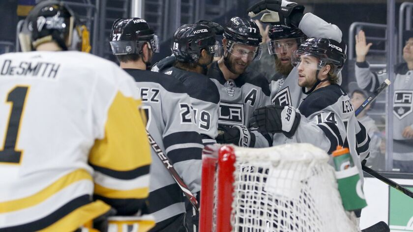 Kings players celebrate a goal against the Penguins during the second period Saturday.