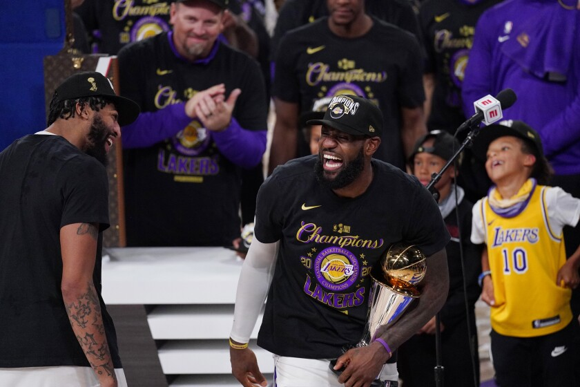 Lakers' LeBron James holds the MVP trophy as he celebrates with Anthony Davis and teammates.