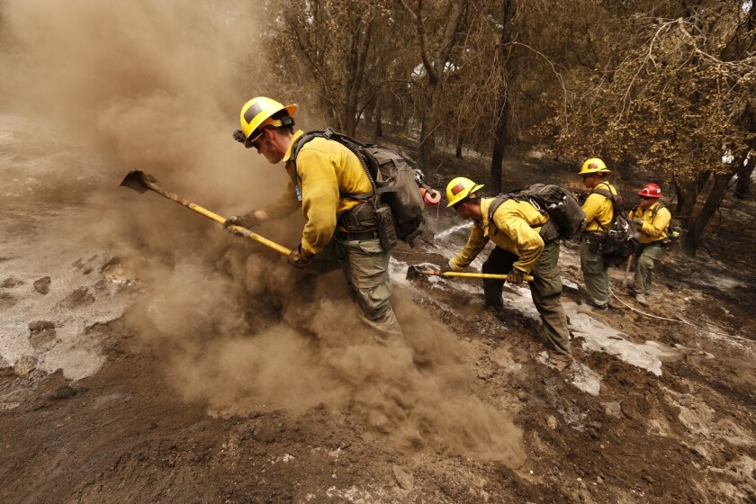 From left, firefighters Aaron Williams, Lyle Bennett, Robert Larios and Capt. Crawford Gunn, with the San Bernardino National Forest, put out hot spots Monday morning along Highway 154 in Santa Barbara County.
