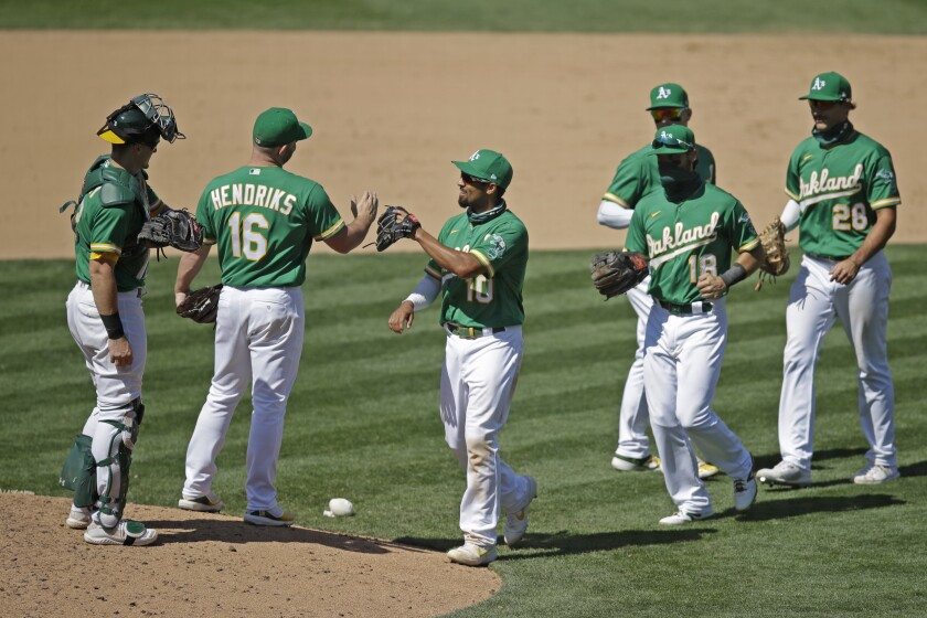 Oakland Athletics' Sean Murphy, Liam Hendriks (16) and Marcus Semien, from left, and teammates celebrate the 3-1 win over the Houston Astros in a baseball game Saturday, Aug. 8, 2020, in Oakland, Calif. (AP Photo/Ben Margot)