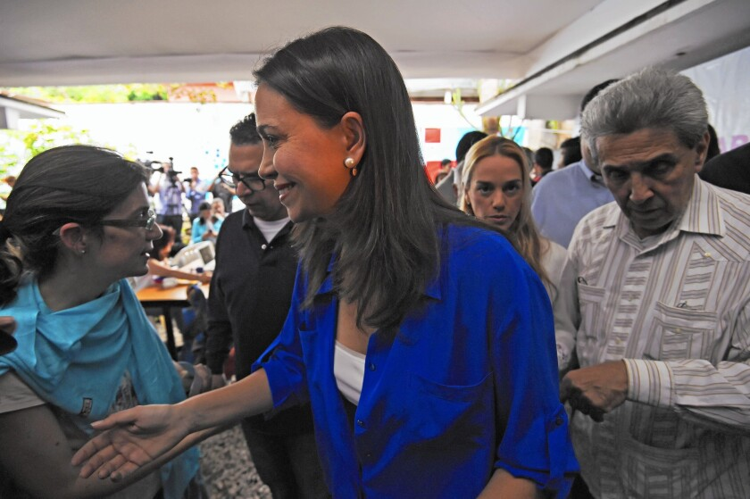 Venezuelan opposition leader Maria Corina Machado speaks with supporters after a news conference. She denied accusations of involvement in a conspiracy to murder the nation's president.