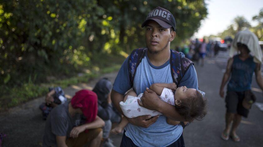Honduran migrant Oscar Hernandez, 22, carries his 11-month-old daughter Daniela, as he walks from Ci