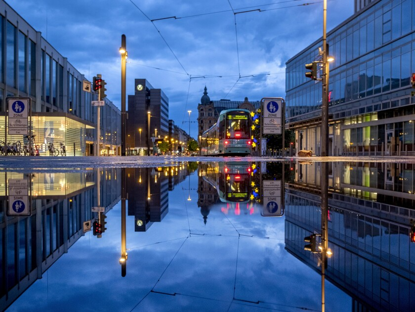 A tram is reflected in a puddle after the city is almost empty shortly after the end of the curfew in central Frankfurt, Germany, Tuesday, May 11, 2021. (AP Photo/Michael Probst)