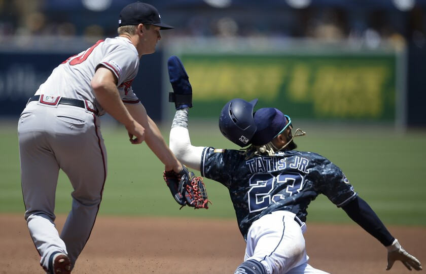 The Padres' Fernando Tatis Jr. avoids a tag by Atlanta Braves pitcher Mike Soroka in the first inning of Sunday's game.