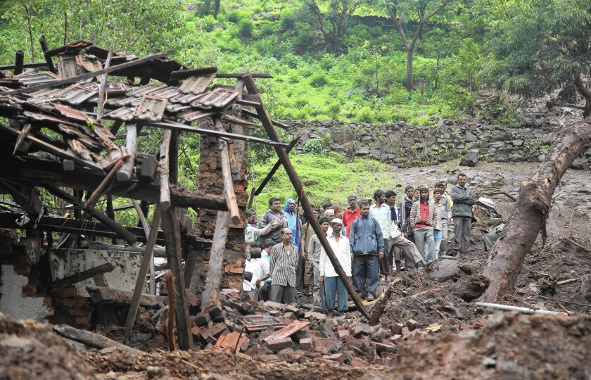 Residents examine damaged homes in India's village of Malin, in the Pune district of Maharashtra state, where heavy rains preceded a deadly mudslide. Environmentalists say deforestation in the area made the slide worse than it might have been.
