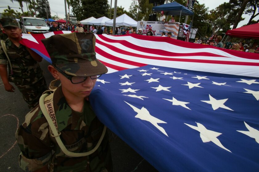 Boys and girls with Eagle Young Marines carry a large U.S. flag down the Fourth of July parade route in Coronado's 67th annual parade.
