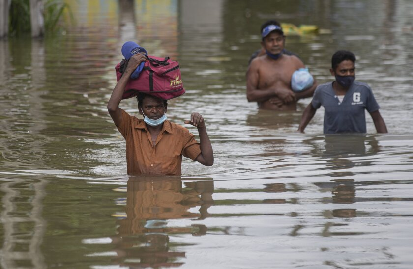 Sri Lankans wade through an inundated street following heavy rainfall at Malwana, on the outskirts of Colombo, Sri Lanka, Saturday, June 5, 2021. Flash floods and mudslides triggered by heavy rains in Sri Lanka have killed at least four people and left seven missing, while more than 5,000 are displaced, officials said Saturday. Rains have been pounding six districts of the Indian Ocean island nation since Thursday night, and many houses, paddy fields and roads have been inundated, blocking traffic. (AP Photo/Eranga Jayawardena)