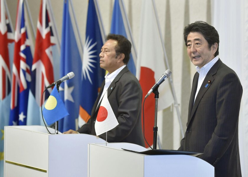 Japanese Prime Minister Shinzo Abe, right, accompanied by Palau's President Tommy Remengesau, speaks following the 7th Pacific Islands Leaders Meeting in Iwaki, Fukushima Prefecture, northeastern Japan Saturday, May 23, 2015. Japan pledged Saturday 55 billion yen ($450 million) in aid to Pacific island nations that are battling rising sea levels and natural calamities as a result of global warming. (Shigeyuki Inakuma/Kyodo News via AP) JAPAN OUT, CREDIT MANDATORY